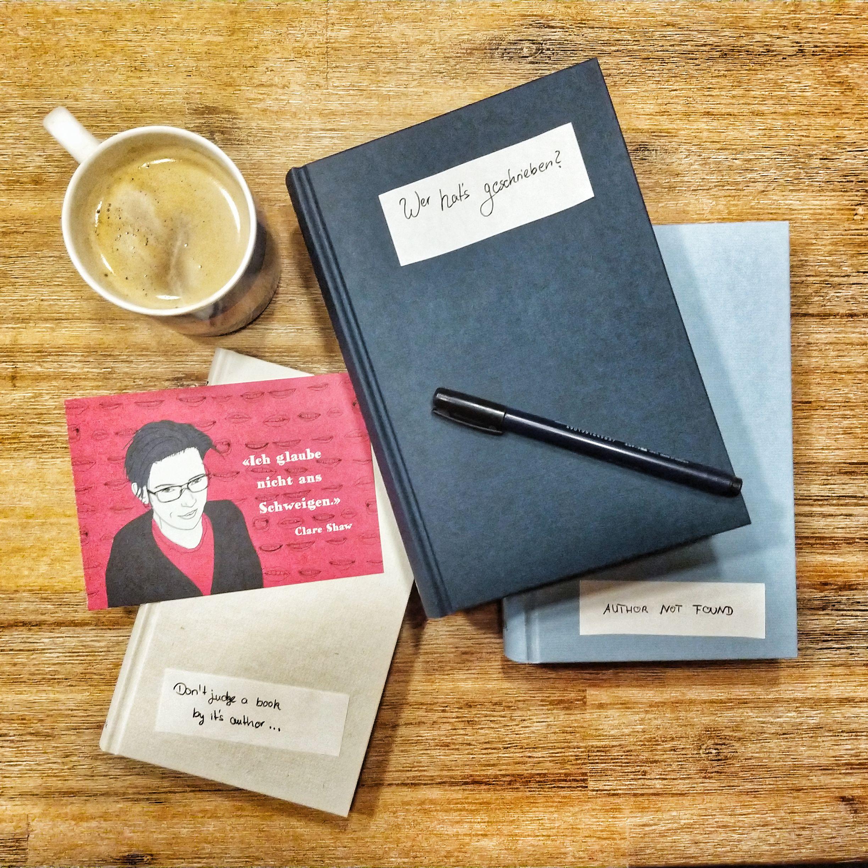"""Drei Bücher ohne Schutzumschlag liegen auf einem Holztisch. Auf einem ist ein Zettel mit """"Author not found"""", auf dem nächsten steht """"Wer hat's geschrieben?"""" und auf dem dritten """"Don't judge a book by it's author ..."""". Oben links steht eine Tasse dampfender Kaffee"""